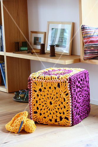 Cubic pouffe with cover made from crocheted granny squares