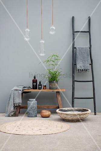 Schwarze Leiter und Holzbank mit Badutensilien vor grauer Wand