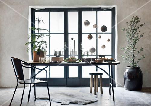 Tisch mit weihnachtlichen Deko-Accessoires vor heller Sprossentür