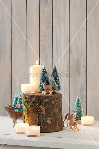 Wintry still-life arrangements with animal figurines, tiny trees and candles