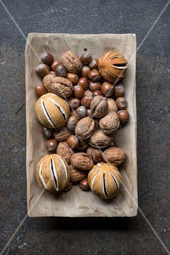Geschlitzte, getrocknete Orangen und Nüsse in einer Holzschale