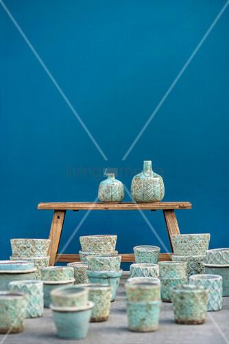 Türkis glasierte Übertöpfe und Vasen auf und vor einer Holzbank