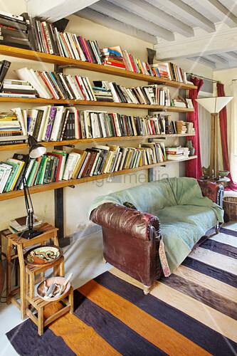 Wohnzimmer im Vintage-Stil mit altem Sofa unter den Bücherregalen