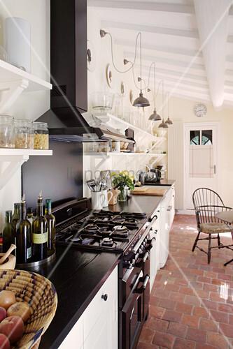 Schmale Landhausküche mit Gasherd und Terracottafliesenboden