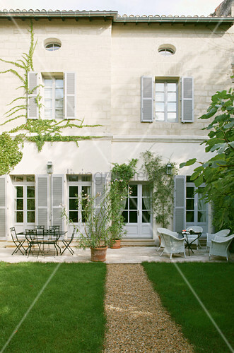 Gravel path flanked by clipped lawns leading to Mediterranean house with terrace
