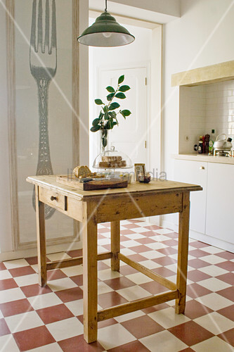 Old table with drawer on chequered tiled kitchen floor