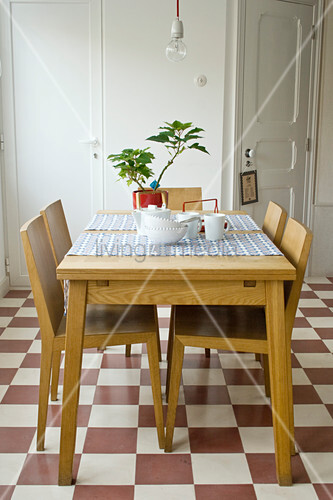 Dining table and chairs on chequered tiled floor