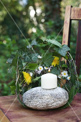 Kerze auf Stein, umgeben von Blätterkranz als Windschutz