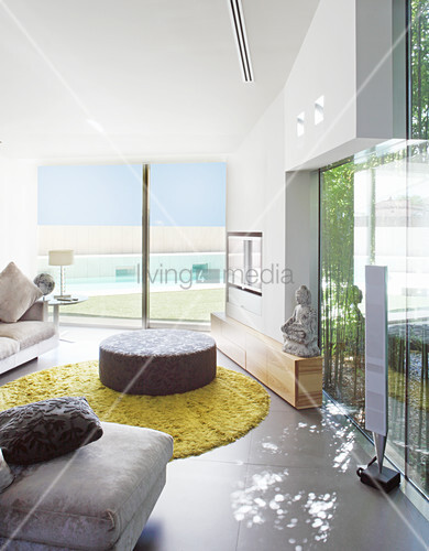 Ottoman in modern living room with glass walls