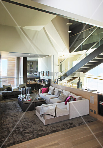 Modern living room with staircase behind glass wall