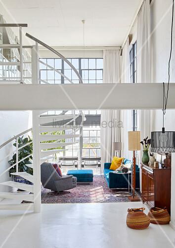 Blaue und graue Polstermöbel und Wendeltreppe in offenem Wohnraum mit doppelter Raumhöhe
