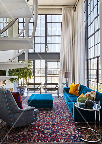 Blue and grey upholstered seating in double-height, open-plan interior with glass walls