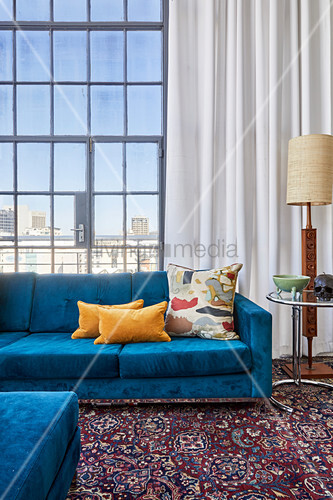 Scatter cushions on bright blue sofa, side table and standard lamp against glass wall in high-ceilinged interior
