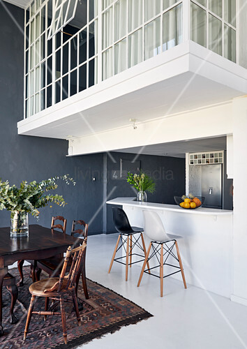White kitchen counter and bar stools below gallery and dining table and chairs in high-ceilinged room