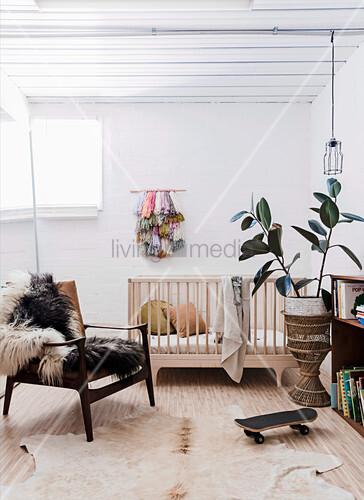 Sessel mit Fell, Gitterbett und Zimmerpflanze im Babyzimmer