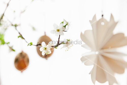 Papierdeko und Ostereier aufgehängt an Obstblütenzweigen