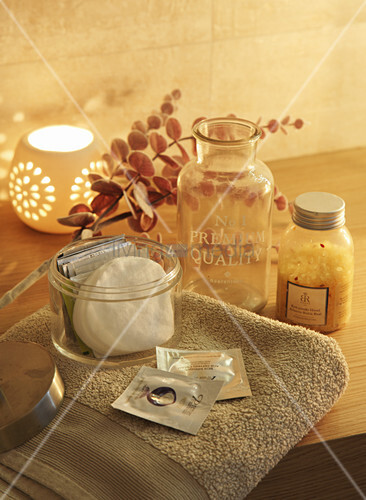Bathroom accessories on towel and candle lantern scattering warm light