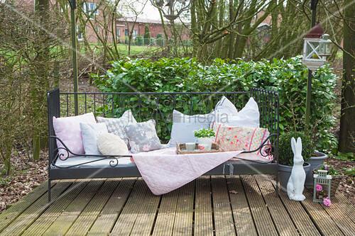 Gartenbank mit Kissen, Decke und Korbtablett, daneben Hasenfigur auf Terrassenplatz