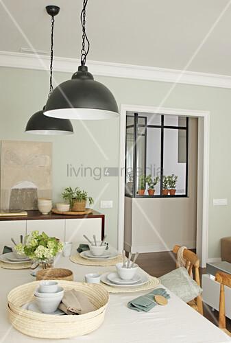 Natürlich gedecker Tisch im Esszimmer mit blassgrüner Wand