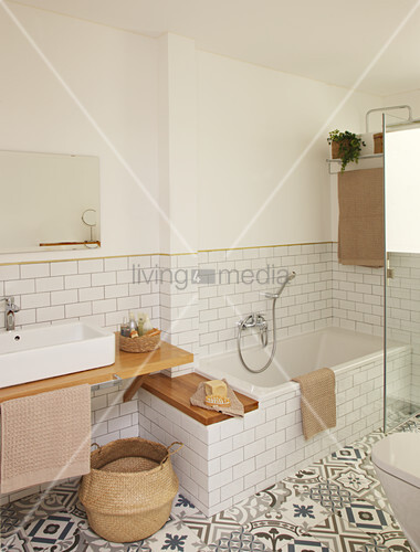 Bathtub, patterned floor and walls tiled to half height in bathroom