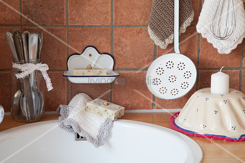 Sink surrounded by cutlery, vintage soap dish, dish cloths, slotted spoon and candle