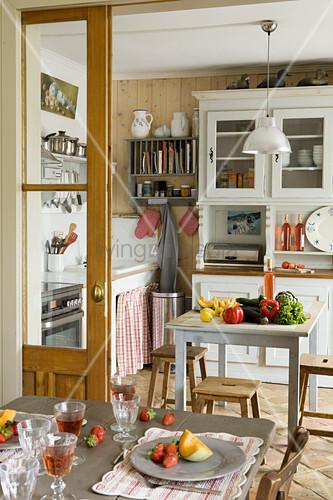 Blick vom gedeckten Esstisch in die gemütliche Landhausküche