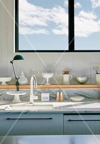 Vintage kitchen utensils on shelf below window