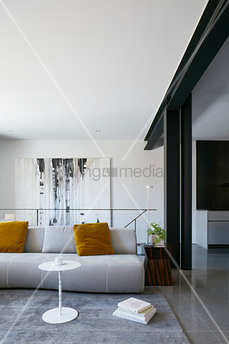 Pale sofa with yellow velvet scatter cushions in modern interior