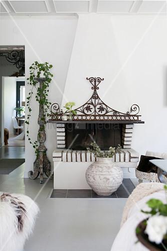 Offener Kamin mit verschnörkelter Metalldeko im Wohnzimmer