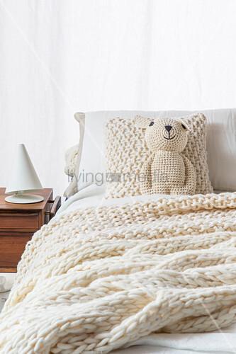 Gehäkelter Teddy, gestricktes Kissen und Plaid auf dem Bett