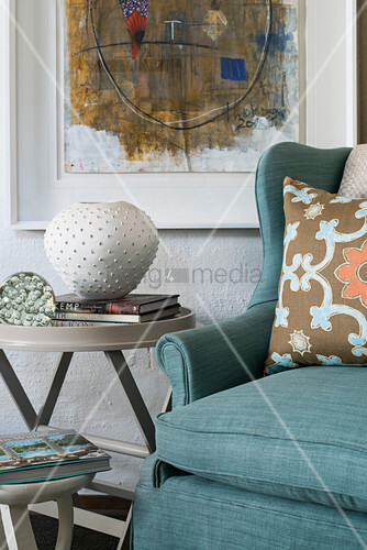 Turquoise armchair and side table below painting on wall