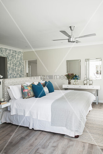 Bed against half-height partition in bedroom