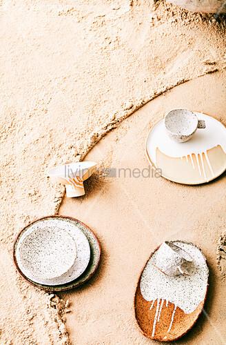 Teller und Tassen mit gesprenkelter und verlaufener Glasur auf Sand