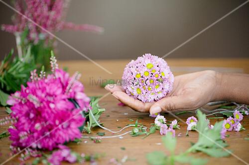 Hand hält Blumenkugel aus Chrysanthemen und Erika