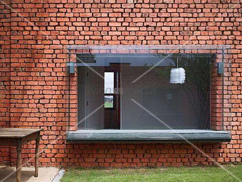 Window seat in modern bay window in old brick wall