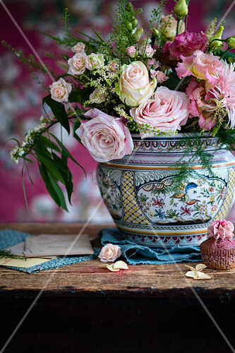 China vase of pink roses and cupcake on rustic wooden table