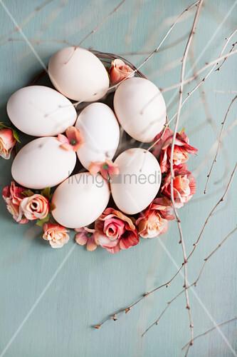 weiße Eier, Rosenblüten und Zweige