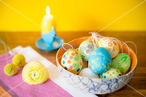 Mit Gouache-Farben bemalte Ostereier, Blume und Kerze