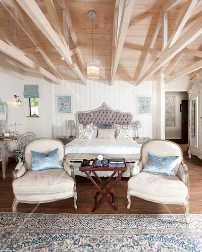 Double bed and two armchairs in elegant bedroom with wooden roof structure