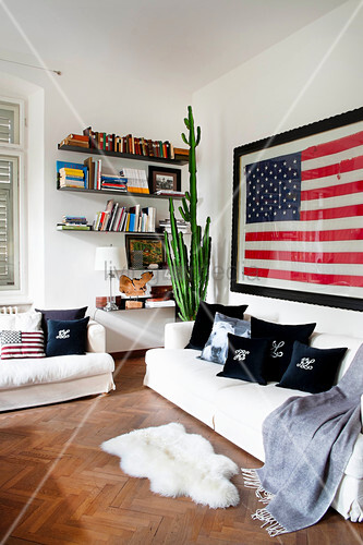 Scatter cushions and blanket on white sofa set, sheepskin rug, wall-mounted shelves, cactus and US flag on wall