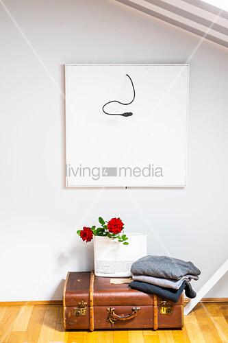Pullover und Geschenktüte mit Rosen auf Vintage Koffer auf dem Boden