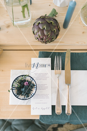 Cutlery and menu on set table