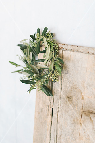 Wreath of flowering olive branches on wooden board