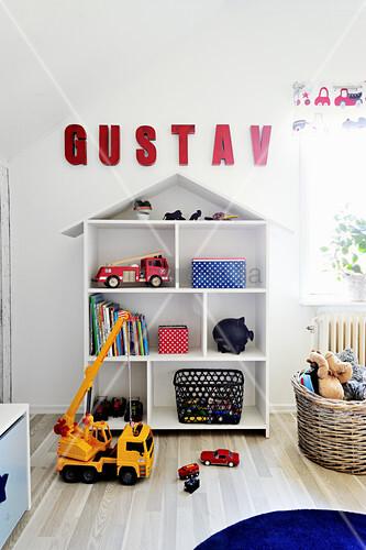 Roter Namenszug über dem Regal in Hausform im Kinderzimmer