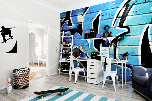 Double desk against graffito mural in teenager's bedroom