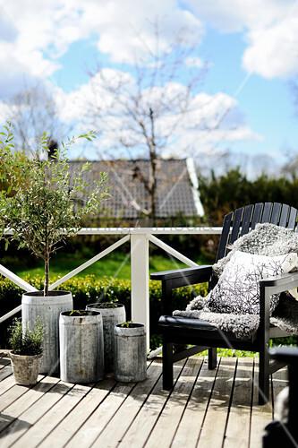 Schwarzer Deckchair und Übertöpfe aus Metall auf der Terrasse