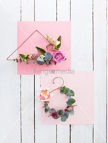 Minimalistische Blumenkränze auf gebogenem Draht und rosa Papier
