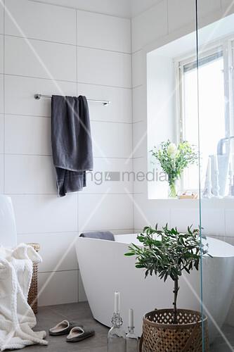 Frei stehende Badewanne im Bad mit weißen Wandfliesen und Fenster
