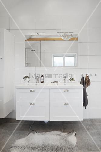 Weißer Waschtischmöbel und Wandspiegel in weißem Badezimer