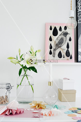 Vase of white lilies and paper rosettes on desk